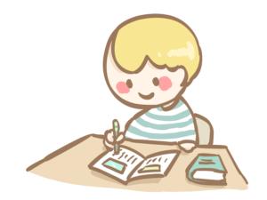 机に座ってペンを握る男の子