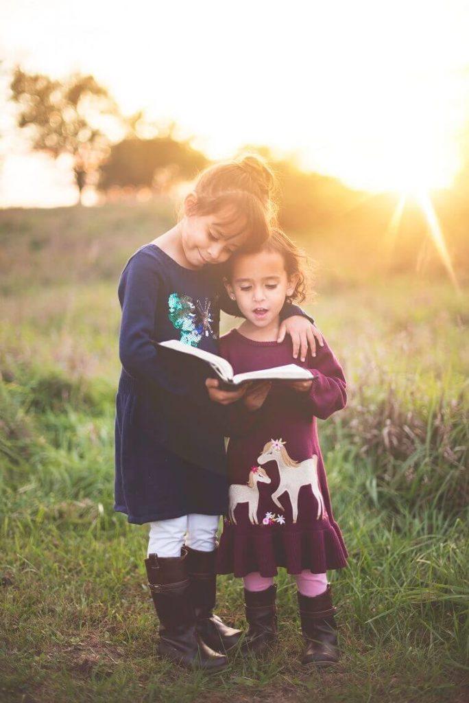 立って一緒に本を読む子供の姉妹