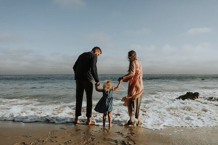 海辺に立つ両親と子供