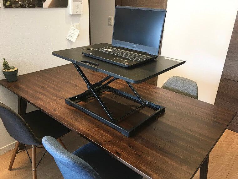 4人掛けダイニングテーブル上にfenge スタンディングデスクを載せてその上にノートパソコン